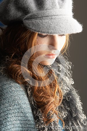 Teenage Girl Wearing Cap And Knitwear In Studio