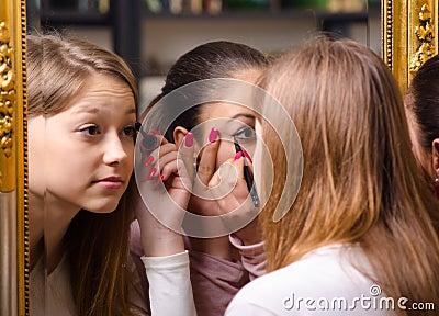 Teenage girlfriends having fun while putting make up