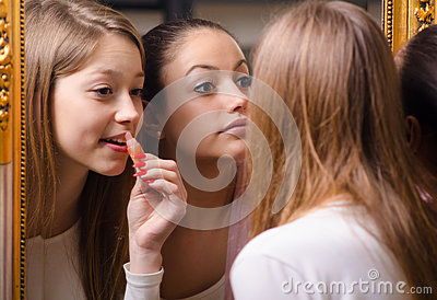 Teenage girlfriends putting make up in front of the old mirror