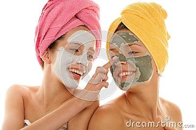Teenage girls applying facial cream