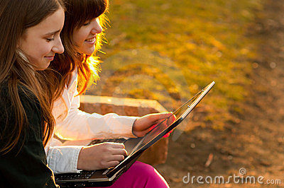 Teenage girls having fun with notebook