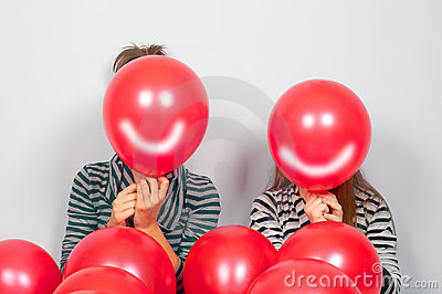 Teenage girls hiding their faces behind balloons