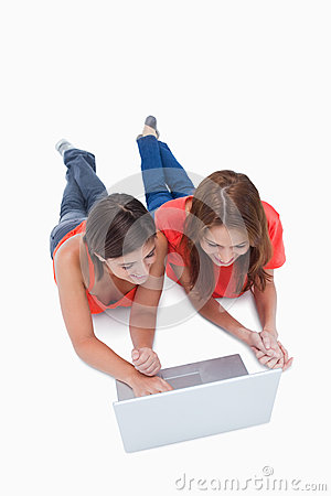 Teenage girls lying down while looking at a laptop