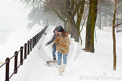 Teenage girls running under the falling snow
