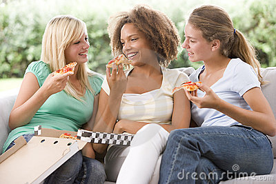 Teenage Girls Sitting On Couch And Eating Pizza