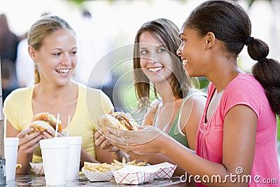 Teenage Girls Sitting Outdoors Eating Fast Food