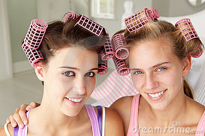 Teenage girls using curlers in their hair