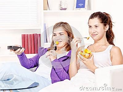 Teenage girls watching tv and eating fruit salad