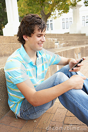Teenage Student Sitting Outside Using Mobile Phone