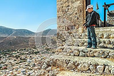 Teenage traveler standing high up on stone steps of ancient Byzantine Castle of Chora on Greek Kalymnos island Stock Photo