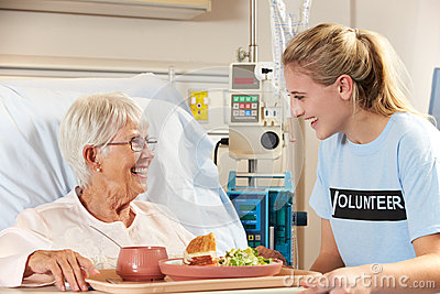 Teenage Volunteer Serving Senior Female Patient Meal