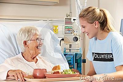 Teenage Volunteer Serving Senior Female Patient Meal