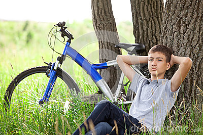 Teenager with a bicycle in the park on the grass