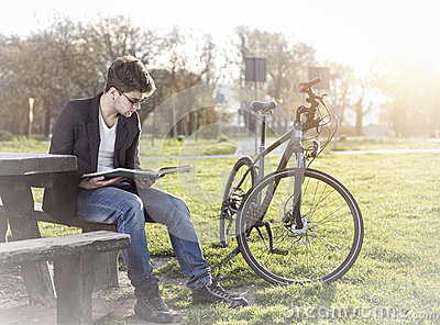 Teenager with bicycle reading book