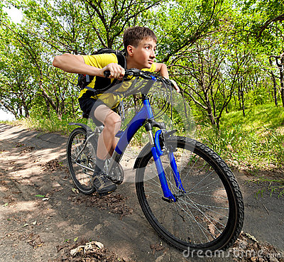 Teenager on a bicycle traveling in the forest
