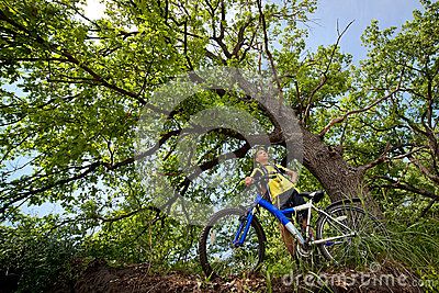 Teenager on a bicycle traveling in the woods