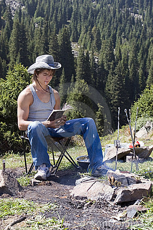 Teenager with  book in mountain hike