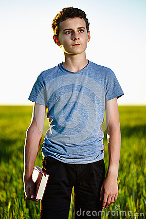 Teenager with a book in a wheat field