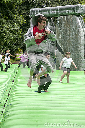Teenager bouncing on an inflatable Stonehenge Editorial Photo