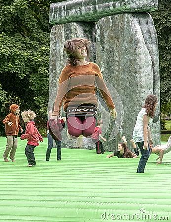 Teenager bouncing on inflatable Stonehenge Editorial Stock Photo