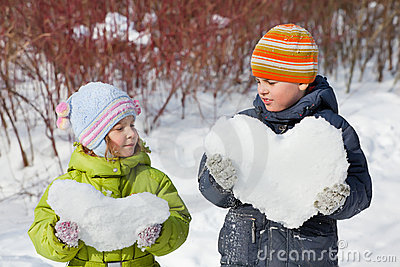 Teenager boy and girl keep hearts from snow