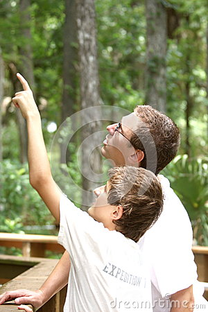 Teenager boy and his father hiking in  summer park