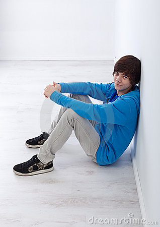 Teenager boy sitting by the wall