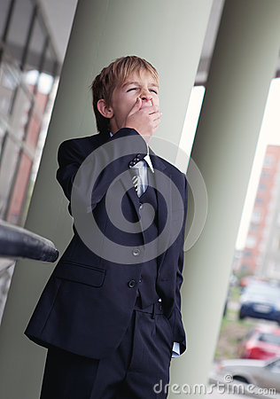 Teenager in business suit yawning