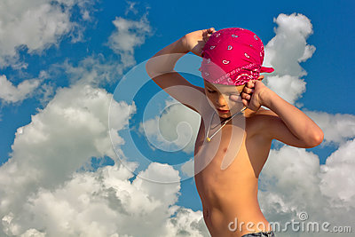 Teenager in crimson bandana hot sunny day on the background of sky and clouds