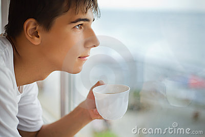 Teenager with cup in hand looking out of window