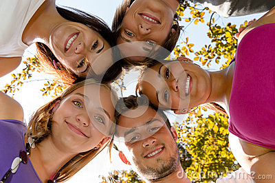 Teenager in einem Kreis, der im Park lächelt