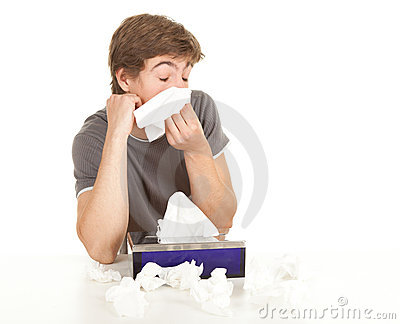 Teenager with flu blowing her nose