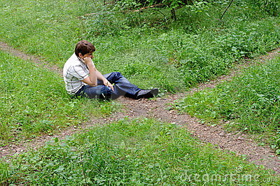Teenager in forest by crossroad choose the path