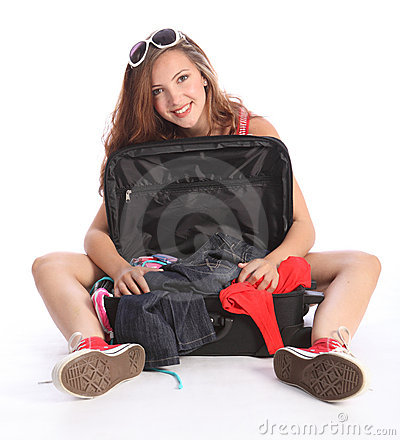 Teenager girl has fun packing for holiday travel