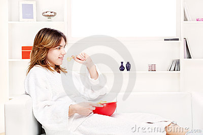 Teenager girl at home eating chips