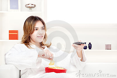 Teenager girl at home watching television