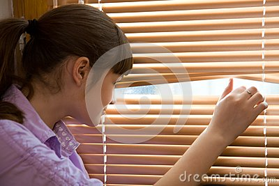 Teenager girl looks out of the window