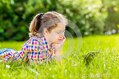 Teenager girl lying on the grass with digital tablet or e-book, outdoor portrait