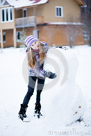 Free Teenager Girl Making Snowman Outdoors In Front Of House Royalty Free Stock Photos - 28764068