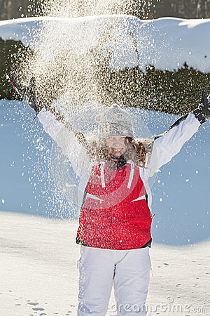 Teenager girl playing with snow in park