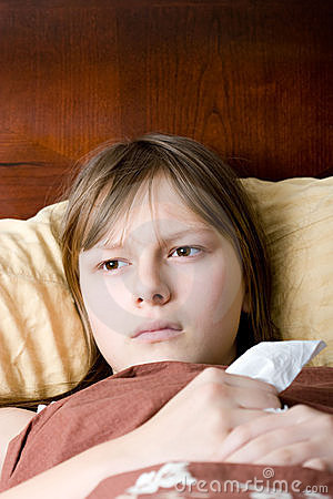 Teenager girl sick with flu lying in bed