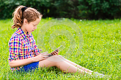 Teenager girl sitting on the grass with digital tablet on her knees