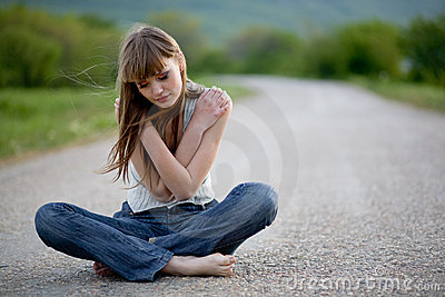 Teenager girl sitting on road
