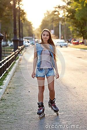 Teenager girl skating during sunset