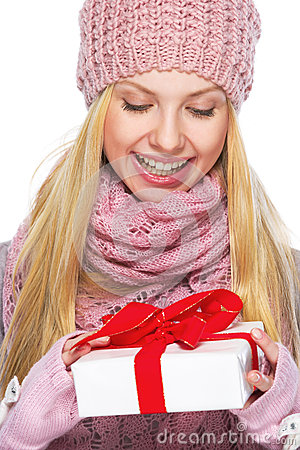 Teenager girl in winter hat and scarf with presenting box