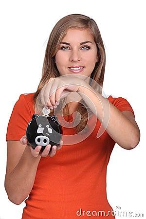 Teenager holding piggy bank