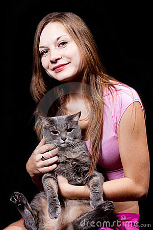 Teenager holds on hands of the big gray cat