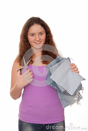 Teenager holds scissors and pieces of jeans.