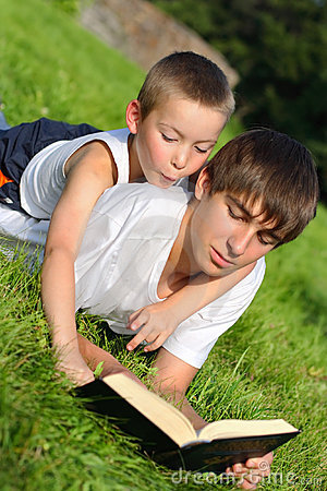 Teenager and kid with a book