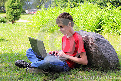 Teenager with a laptop in the park